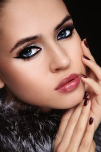 Close-up portrait of young beautiful woman with trendy make-up